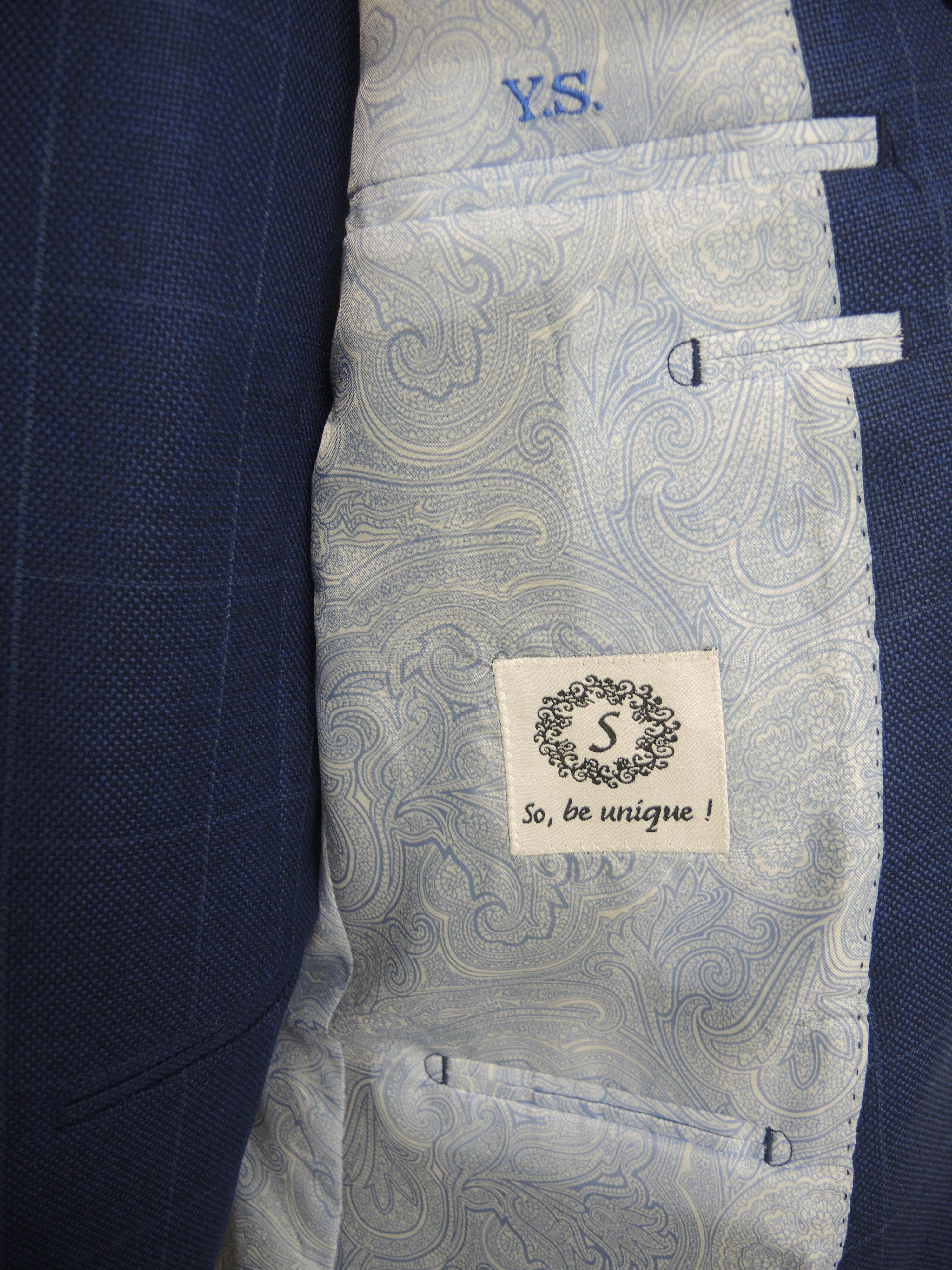 Vue de l'intérieur d'une veste de costume avec doublure bleue claire, initiales et logo