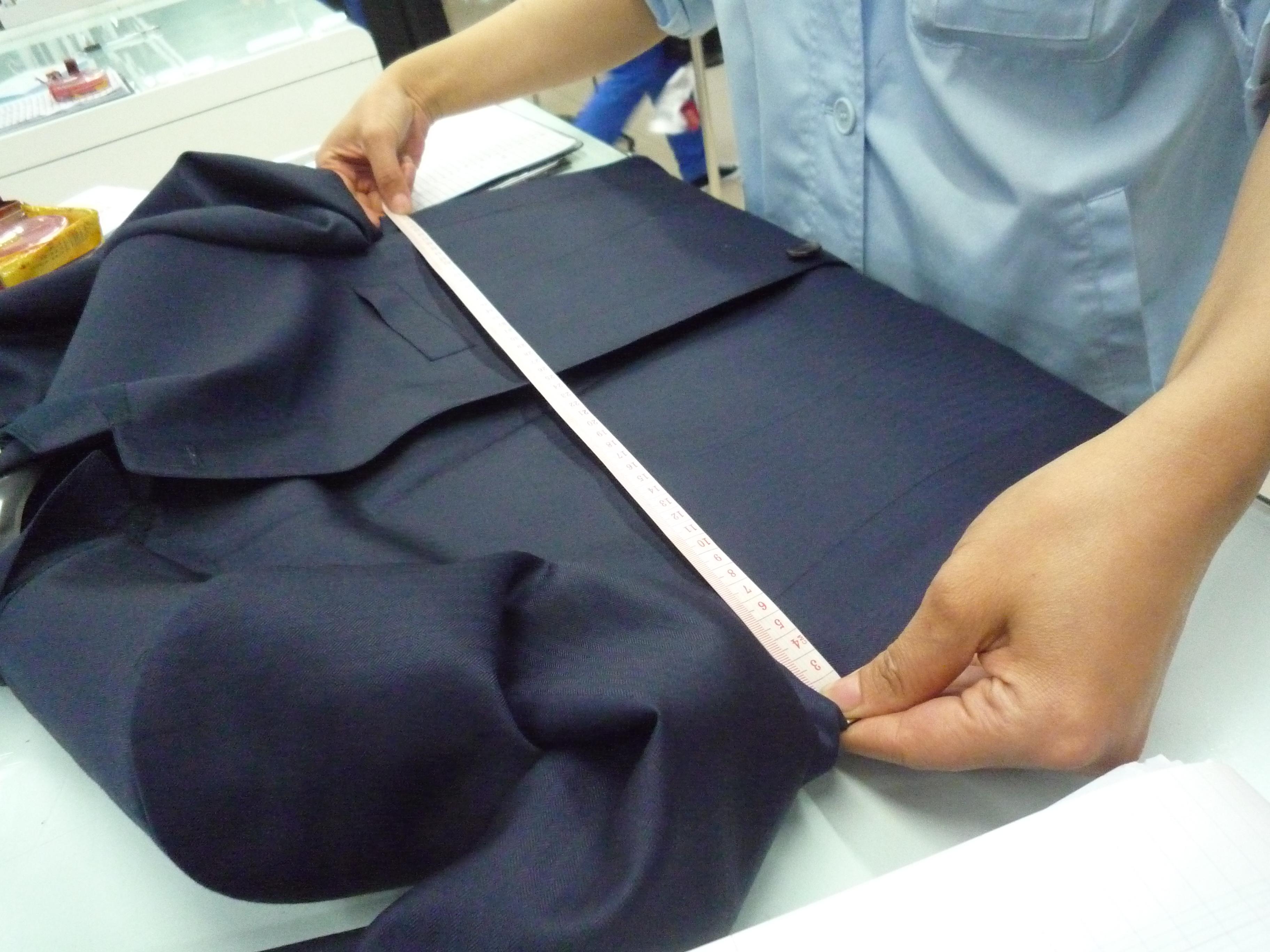 Femme qui contrôle la largeur du torse d'une veste de costume